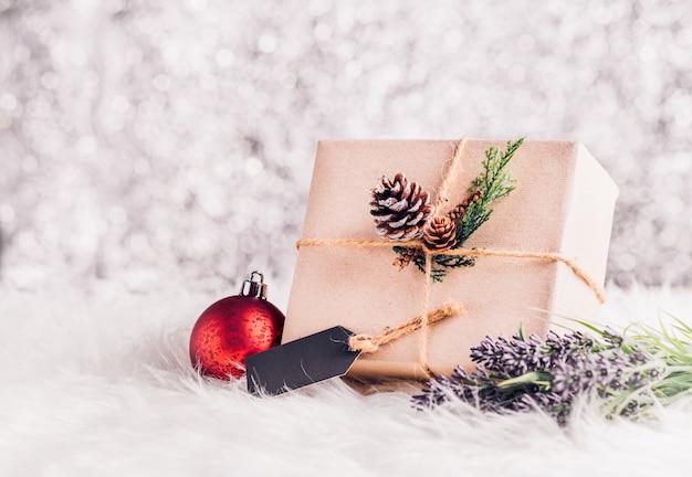 茶色のペーパークラフトは、ラベルのタグで現在の箱にひっくり返され、松のコーンとクリスマスで飾る