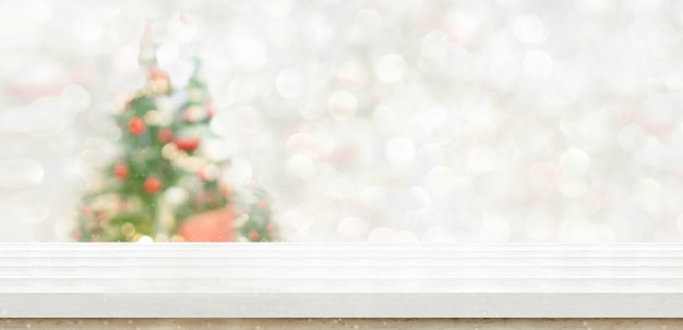 文字列の明るい背景を持つぼかしボケクリスマスツリーの装飾で白い大理石のテーブルトップ