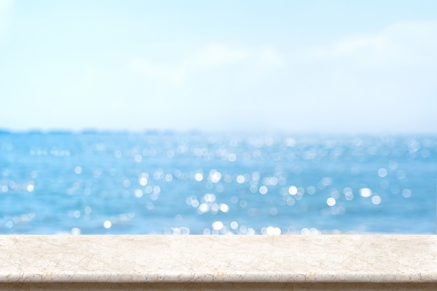 ぼやけたボケ海と青い空と白い大理石のテーブルトップ