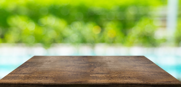 空の堅い木のテーブルとぼやけたヘッジとプール