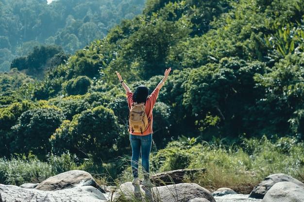 アジアの女性旅行者の岩の上に立っていると風景で空気中の腕