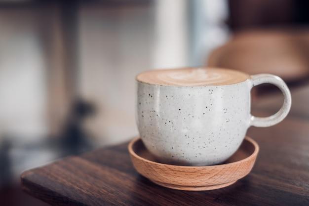 カフェで木のテーブルにカフェラテアートと木のトレイにホットカプチーノコーヒーカップ
