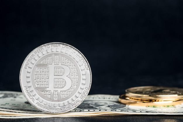 Криптовалюты золотые биткойны на фоне банкноты доллара. виртуальные цифровые деньги