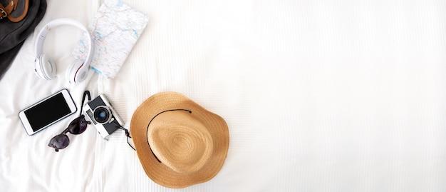 ベッドの上の毛布の上の夏の旅行アイテム。アクセサリー旅行のトップビュー