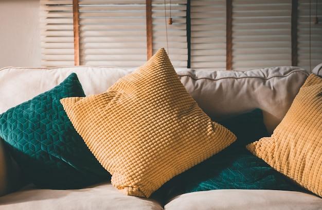 Закройте вверх по подушке на софе дома в утре с солнечным светом. мебель в доме