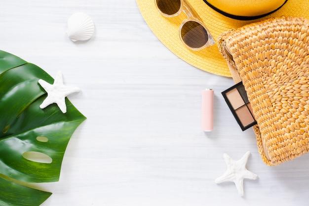 白い木製のテーブルの上の夏のアイテム。モンステラの葉と枝編み細工品バッグ、化粧品。