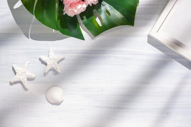 夏のモンステラとシェルと日光の影と白い木のテーブルのヒトデ。