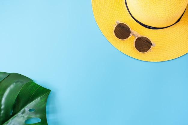 黄色の帽子、サングラス、ブルーのモンステラの葉と青い夏バナー