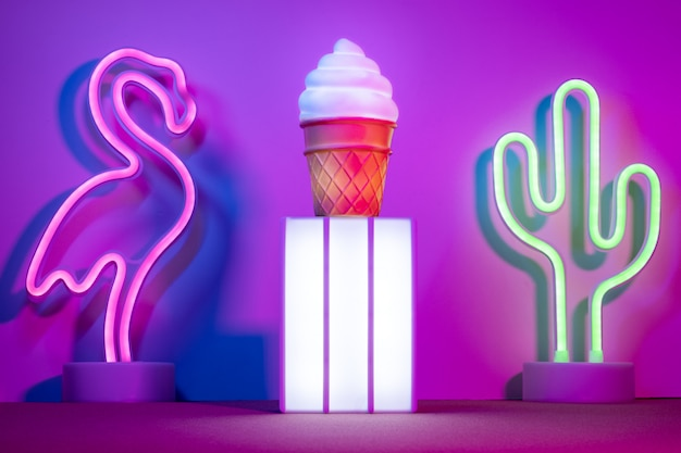 ライトボックスとフラミンゴ、サボテンとテーブルの上のネオンピンクと青と緑の光とアイスクリームの夏