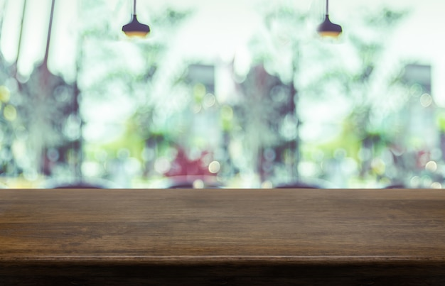 ぼやけたカフェレストランの背景を持つ空の木製テーブルトップ