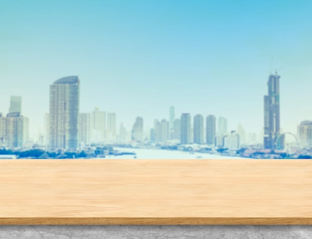 茶色の木のテーブルトップと都市の建物の風景を望む白い大理石ベース