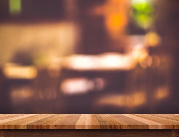 空の茶色の木製テーブルとぼやけたレストランボケ明るい背景