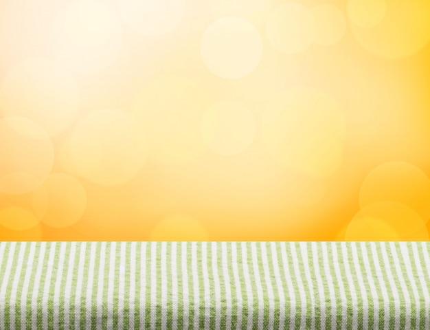 オレンジ色のボケの明るい背景で空の緑のテーブルクロストップ