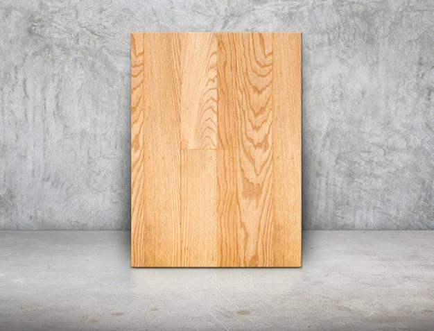 グランジ灰色のコンクリートの壁と床にもたれて空白の木製ブロックフレーム