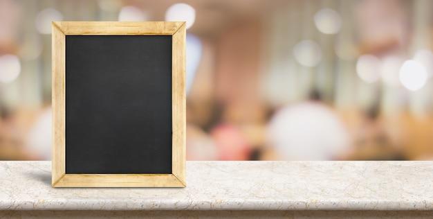 レストランの背景で食事の人々のぼかしの前に大理石のテーブルに空の黒板