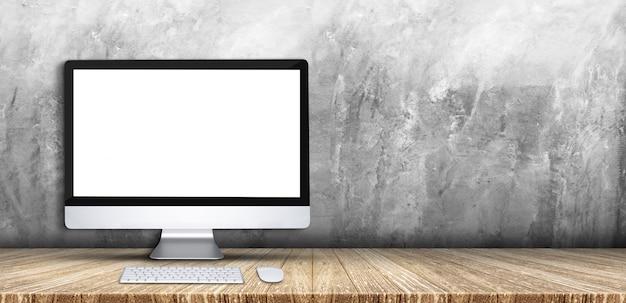 デスクトップコンピューター、キーボード、木の板テーブルトップグレーグランジコンクリート壁の背景上のマウス