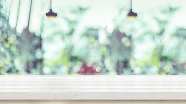コーヒーショップのぼやけた窓と空の白い板木製テーブルトップ