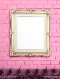 豪華な紫のソファの上のピンクのレンガの壁に掛かっている空白の黄金ビンテージビクトリア朝様式の額縁