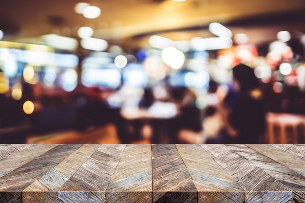 空の古いグランジ木の板テーブルトップと背景のボケ味のレストランで人々の夕食をぼかし