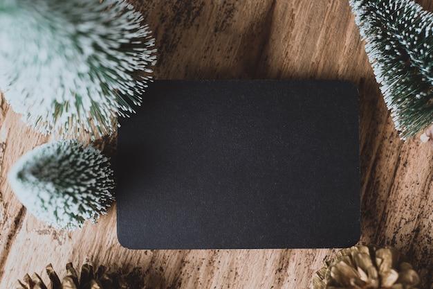 グランジ木製テーブルにクリスマスツリーとゴールドパインコーンと空の黒板のトップビュー