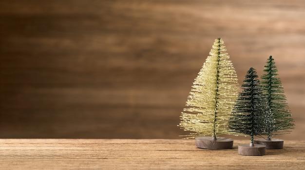 メリークリスマスの木製の壁と木製のテーブルの上のクリスマスツリー