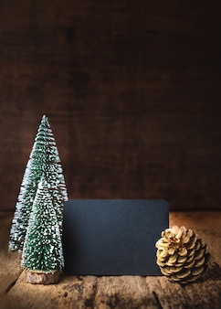 メリークリスマスと新年あけましておめでとうございます黒板に木のテーブルと壁にツリーとゴールドパインコーン