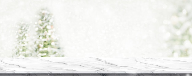 ぼかしのクリスマスツリーの文字列の大理石のテーブルライトは雪で背景をぼかし