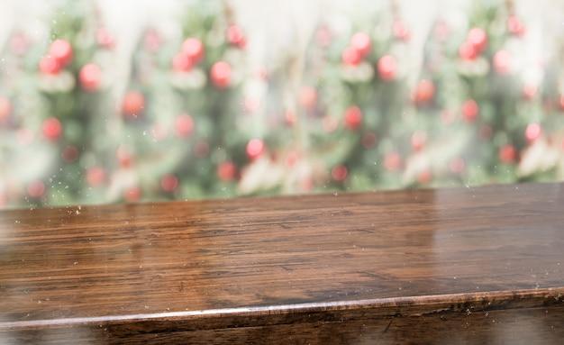 抽象的なテーブルトップは、クリスマスツリーの赤い装飾ボールと雪のボケ味を持つ背景をぼかし