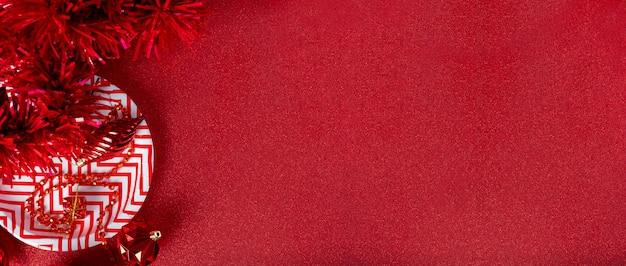 メリークリスマスの赤い背景。見掛け倒し、ギフトボックス、ボール、リボンのトップビューを輝くテーブルに飾る
