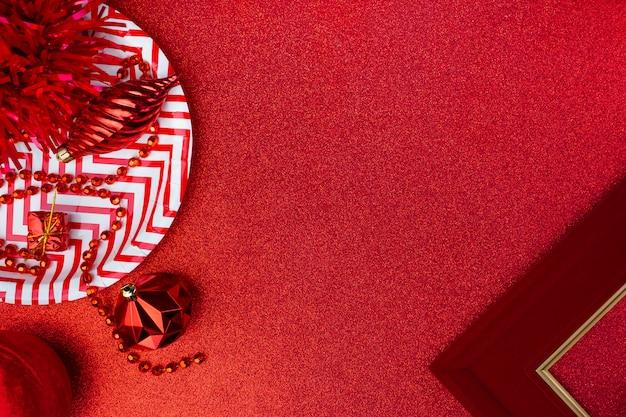 メリークリスマスと新年の赤。見掛け倒し、ギフトボックス、ボール、リボンのトップビューを輝くテーブルに飾る