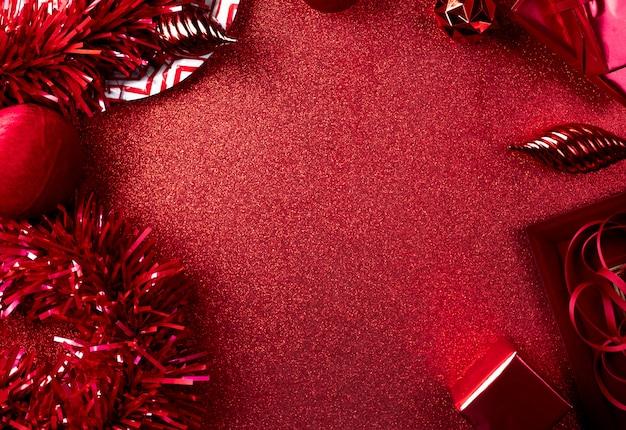メリークリスマスと新年の赤い背景見掛け倒し、ギフト、ボール、リボンのトップビューをテーブルに飾る