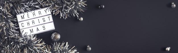 黒いテーブルの背景にメリークリスマスと新年のライトボックス。見掛け倒し、バルーンテーブルのトップビュー