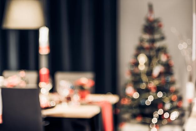 ボケ味を持つ家の台所のテーブルで文字列の光で抽象的なぼやけたクリスマスツリーの装飾