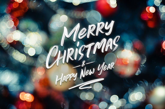 メリークリスマスと新年あけましておめでとうございます単語クリスマスボールのボールとストリングライトの抽象的なボケ味