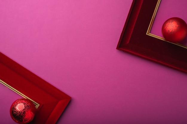 Веселого рождества и счастливого нового года фиолетовый фон. вид сверху мяч, рамка для картины украшают на столе