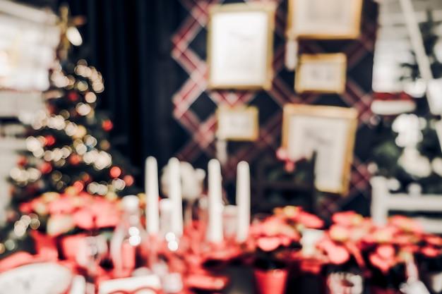 キッチンテーブルで文字列の光でぼやけたクリスマスの装飾
