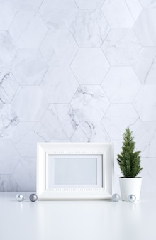 Белая винтажная фоторамка с елкой, шишкой и декором новогодний шар на белом столе