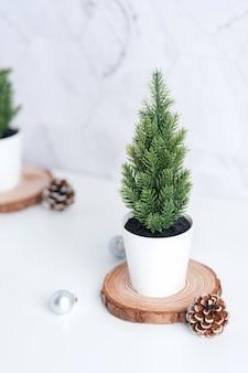 松ぼっくり、白いテーブルと大理石のタイル壁で木製ログに装飾クリスマスボールとクリスマスツリー