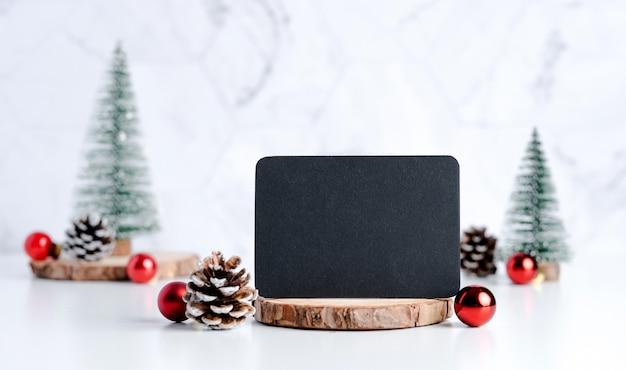 白いテーブルに松ぼっくりと装飾クリスマスボールとクリスマスツリーと黒板