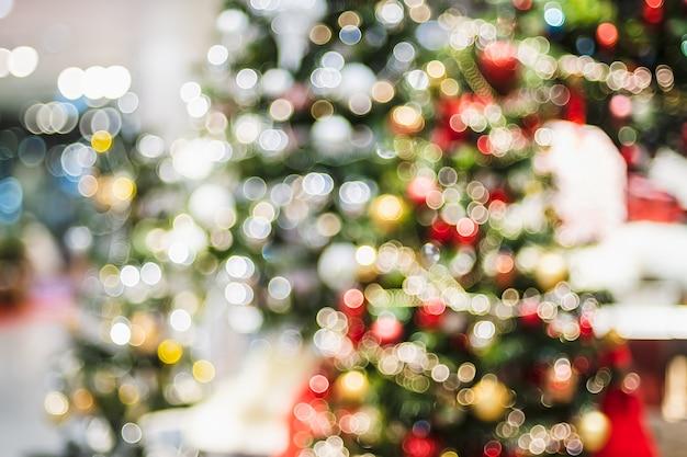 Абстрактный боке елки украшают шар и струнные огни