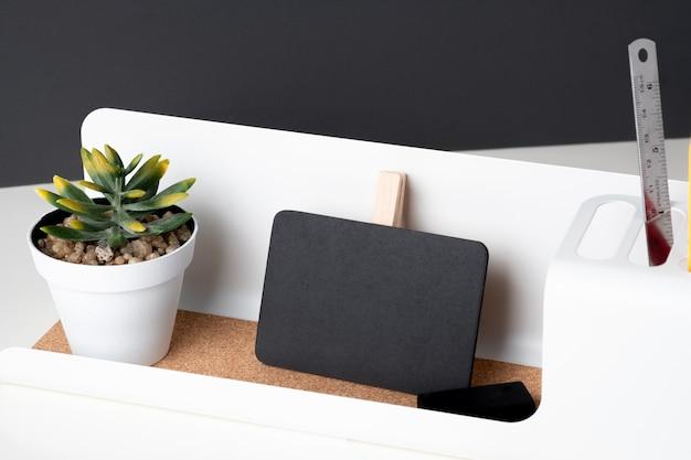 モダンな鉛筆ボックスに黒いクリップ黒板とテーブルの上の白い鍋に緑の植物、オフィスの机に暗い灰色の壁