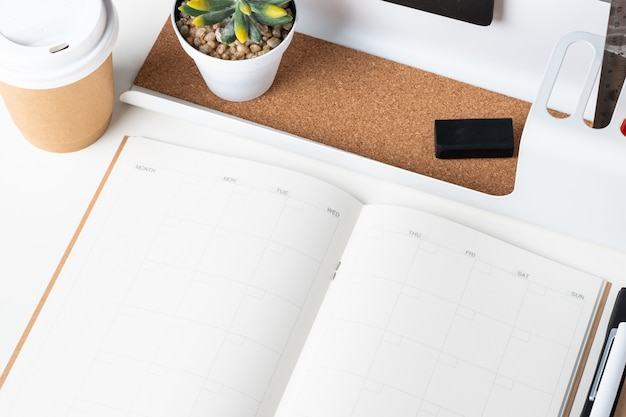 Вид сверху открытого календаря с современными канцелярскими принадлежностями и забрать чашку кофе на белом столе в офисе