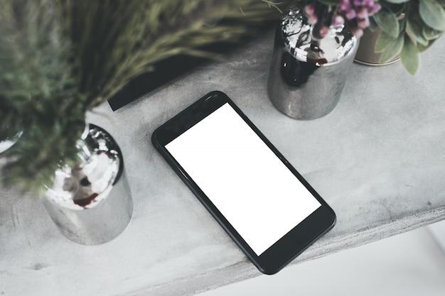 Вид сверху пустой белый экран мобильного на бетонном столе с завода в вазе