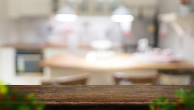 ぼやけた前景の葉とぼやけた家庭の台所と空の暗い茶色の木製テーブルトップ