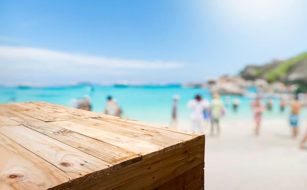 Стойка еды пустой деревянной планки с запачканным туристом на пляже