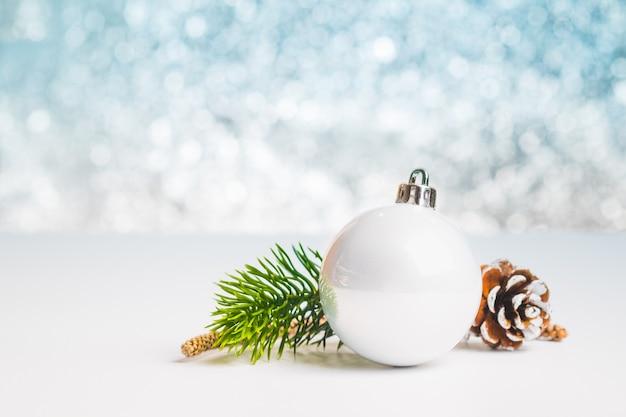 白いクリスマス光沢のあるボールのグループを閉じて、輝く青いボケ抽象的なぼかし背景、休日の季節のグリーティングカードで、白のテーブルにテキストを追加するスペースを残す