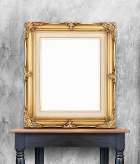 空のヴィンテージゴールデンフォトフレームは、灰色の木製のコンクリートの壁に傾く木製のテーブル
