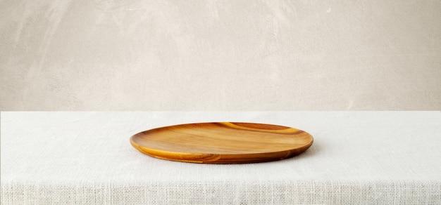白い背景に袋のテーブルクロスの上にある空の木製トレイ。