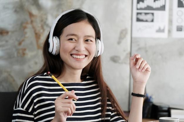 Молодая азиатская женщина в наушниках, улыбаясь с счастью во время работы в офисе