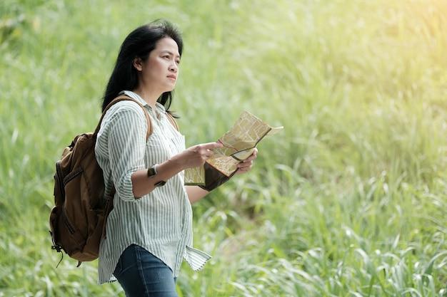 緑の自然の背景を旅行中にアジアの女性の旅行者の地図を保持